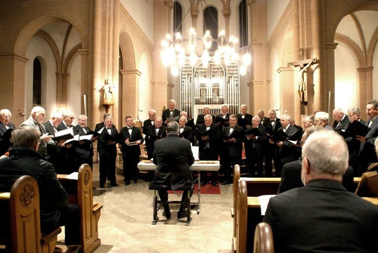This shows older men singing in a choir