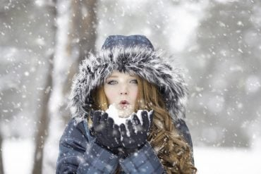 This shows a lady in the snow, blowing snowflake and smiling
