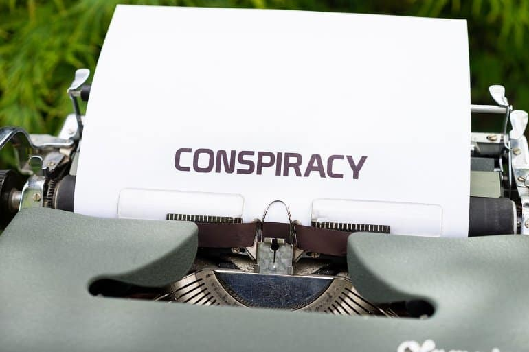 This shows a typewriter with the word Conspiracy typed out on a piece of paper