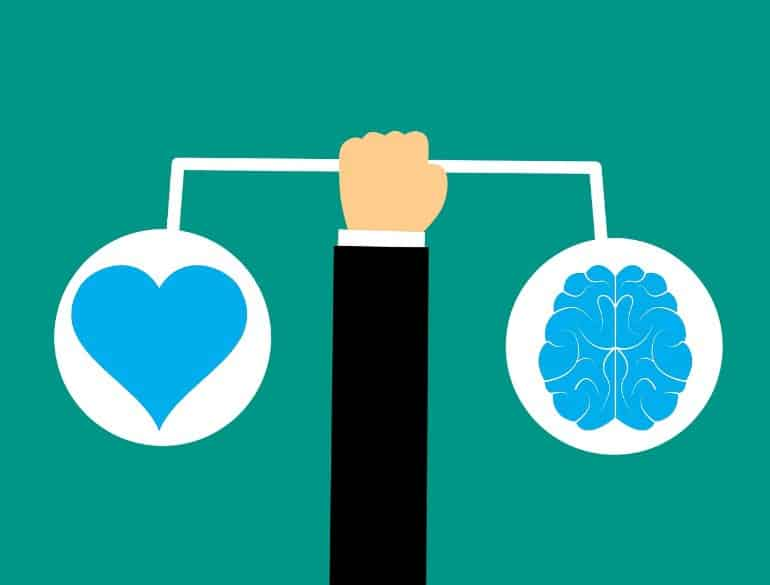 This is a cartoon of a hand holding a scale with a heart and a brain on each side