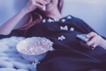 This shows a woman with a TV remote in her hand, eating popcorn