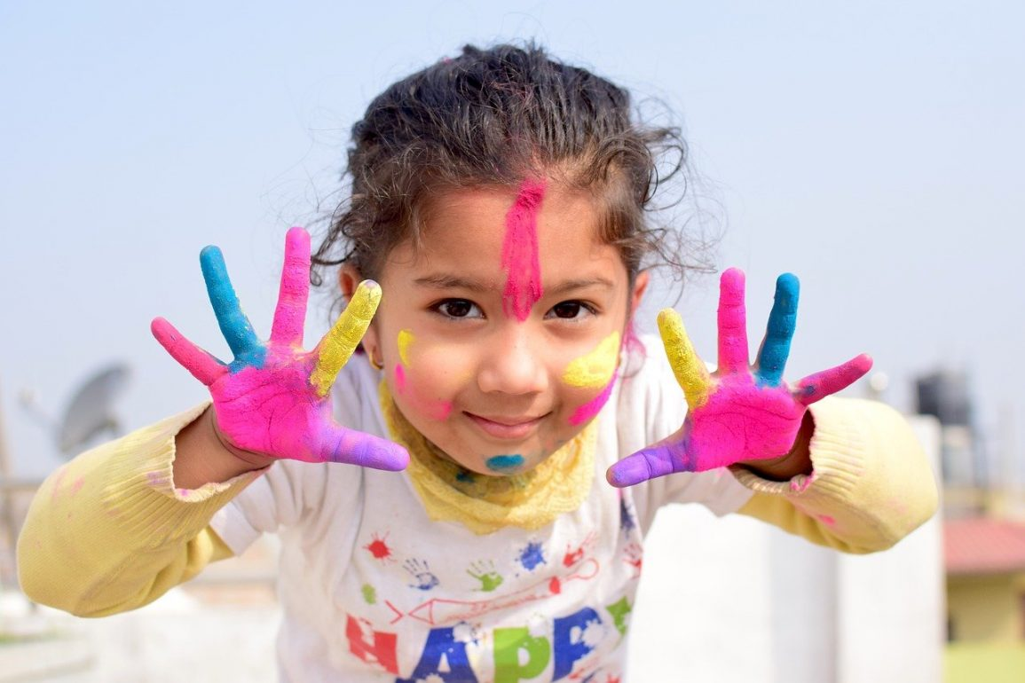 This shows a happy little girl with her hands painted up like a rainbow