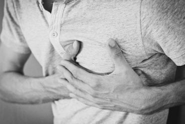 This shows a man clutching his chest as though he is in pain