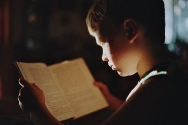 This shows a boy reading a book