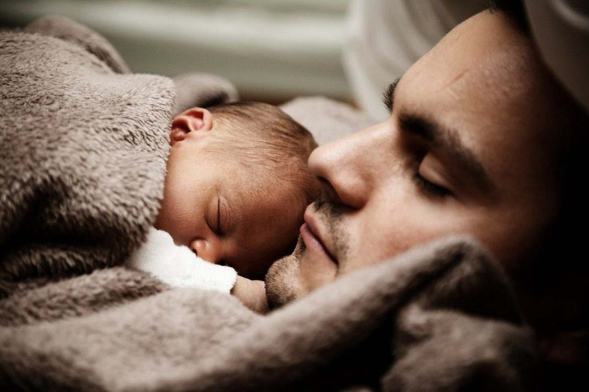 This shows a dad holding his sleeping baby