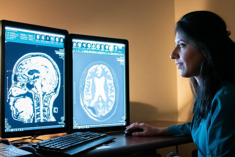 This shows the researcher looking at brain scans on a computer