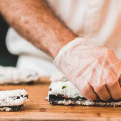 This shows a chef's hand making sushi