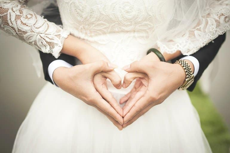 This shows a bride and groom making heart signs with their hands