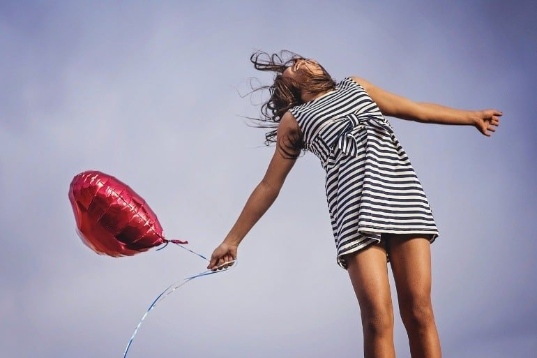 This shows a happy woman, jumping for joy and holding a red heartshaped balloon