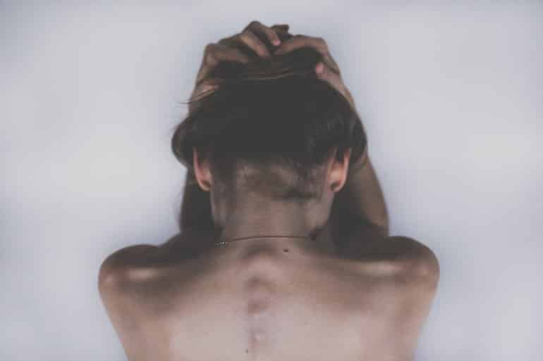 This shows the back of a woman clutching her head