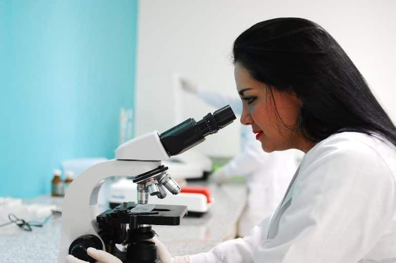 This shows a female scientist looking in a microscope
