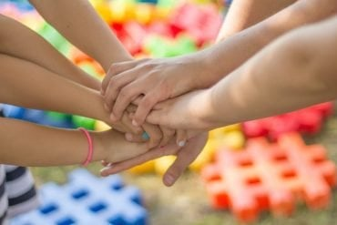 This shows children all putting their hands on top of one another