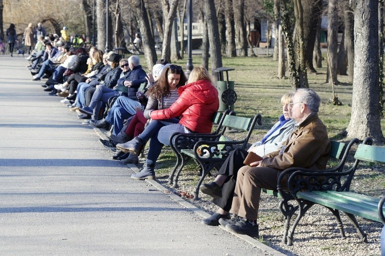This shows old and young people in a park