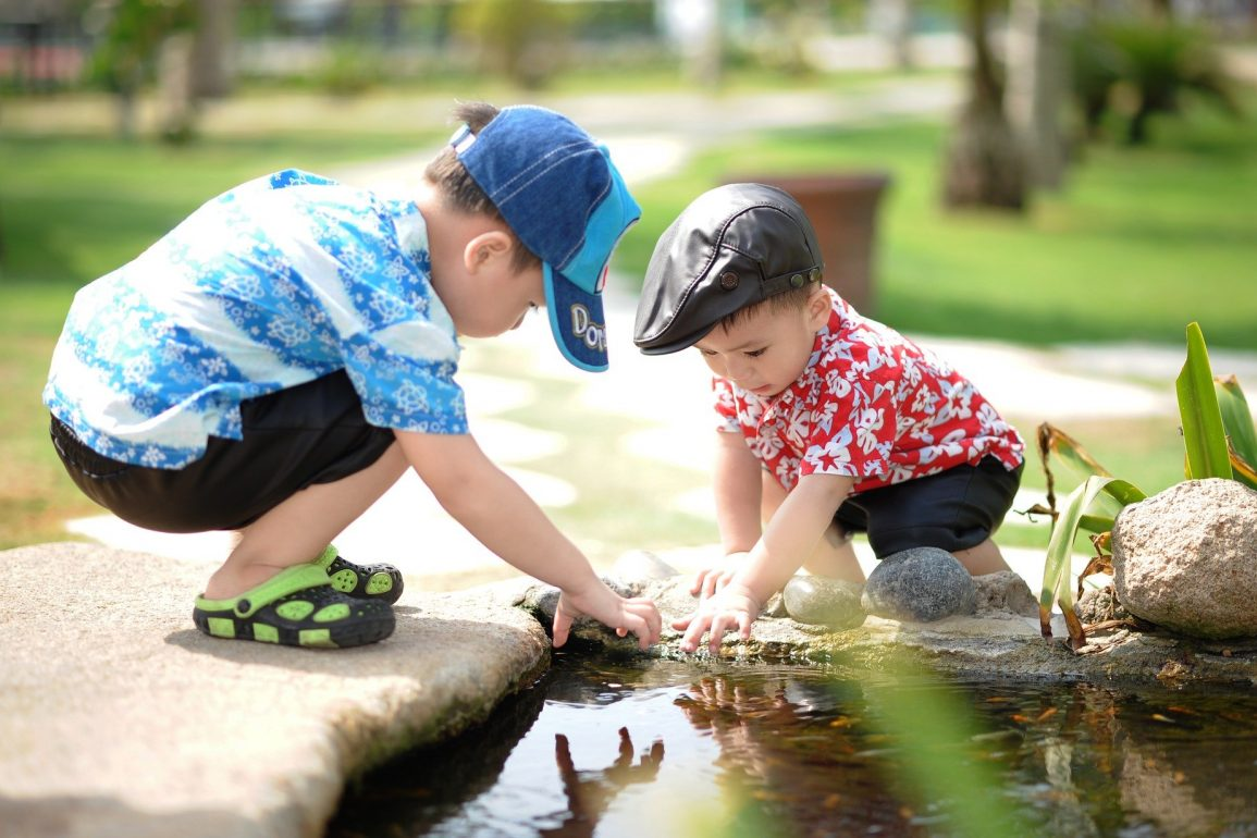 This shows two little boys playing in a stream