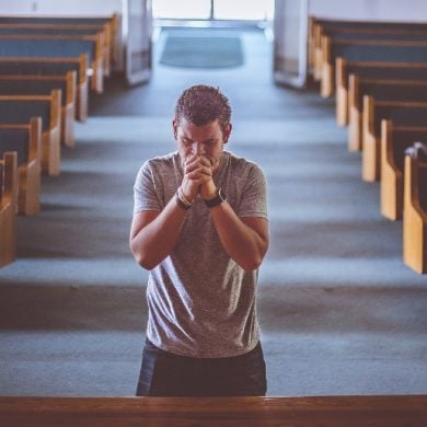 This shows a man praying in a church