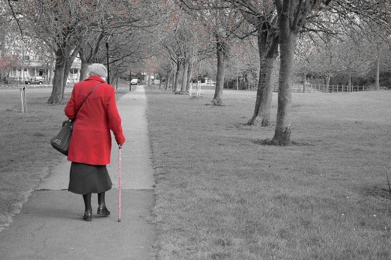 This shows an older lady walking in a park with a cane