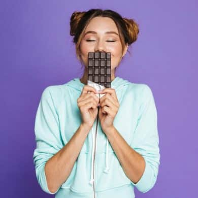 This shows a woman smelling a bar of chocolate