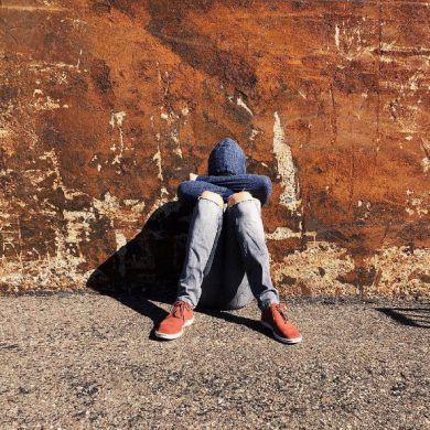 This shows a teenager huddled up against a wall