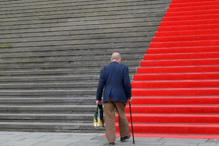 This shows an older man walking up some steps