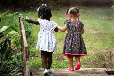 This shows two little girls walking in a park