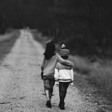 This shows a little boy and girl walking down a dusty road