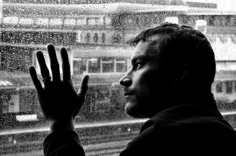 This shows a sad looking man looking out of a window at the rain