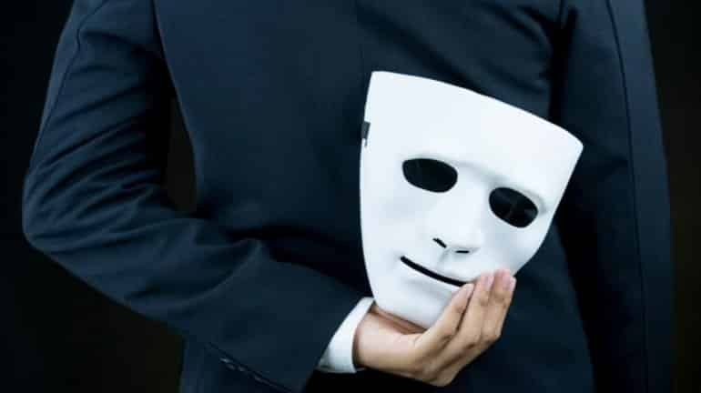 This shows a man holding a mask behind his back