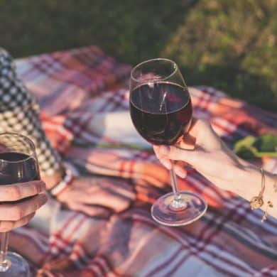 This shows a lady enjoying a glass of red wine