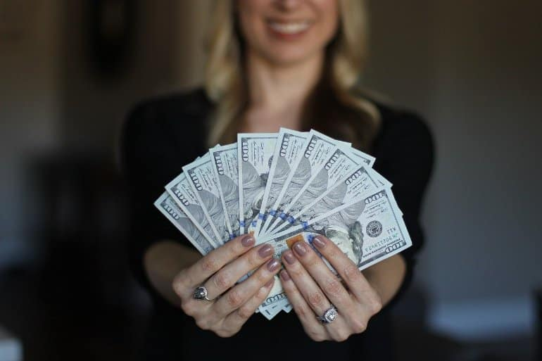 This shows a woman holding $100 bills