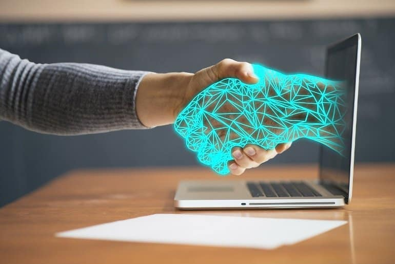 This shows a man shaking hands with a computer generated hand coming out of a laptop