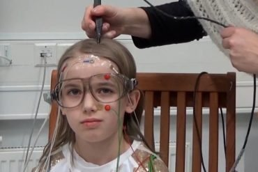 This shows a little girl with an EEG cap on