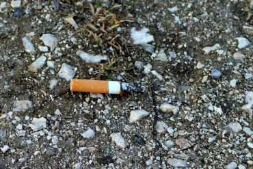 This shows a cigarette butt on the ground