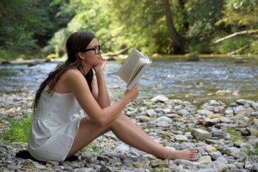 This shows a woman reading by a river