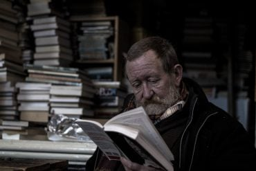 This shows an older man reading a book in a bookstore
