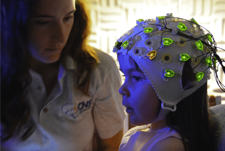 This shows a little girl in an EEG cap with the researcher