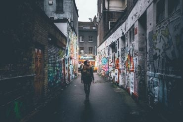 This shows a woman walking down a graffiti covered alleyway