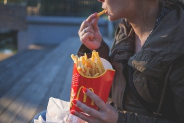 This shows a woman eating fries