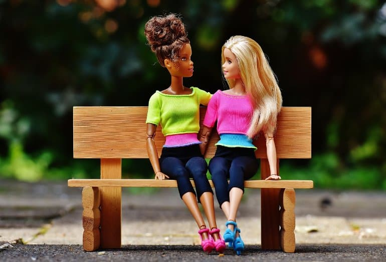 This shows two barbie dolls sitting on a bench