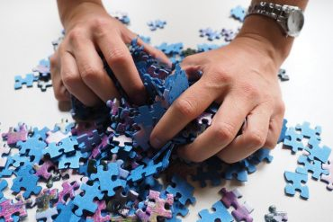 This shows a woman's hands sorting through jigsaw pieces