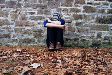 This shows a depressed looking teenage boy sitting next to a wall