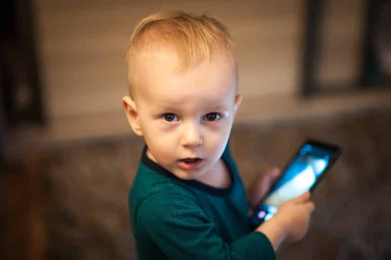 This shows a toddler playing with a smart phone