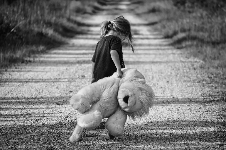 This shows a sad little girl with an oversized cuddly lion