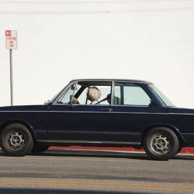 This shows an older lady driving a vintage car