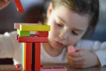 This shows a little girl playing with building blocks