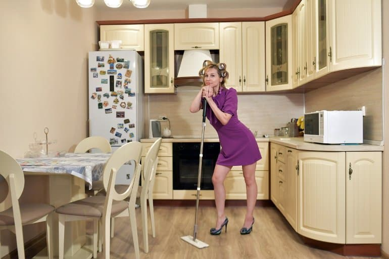 This shows a lady mopping her kitchen floor