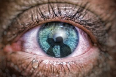 This shows a man's green eye with a reflection of two people kissing in it