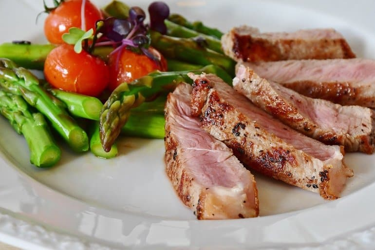 This shows a dinner plate with asparagus and pork tenderloin