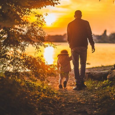 This shows a dad and his little girl on a nature walk at sunset