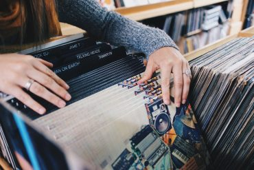 This shows a woman flipping through records in a record store