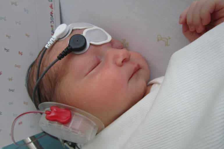 This shows a newborn with a headset and eeg wires on her head